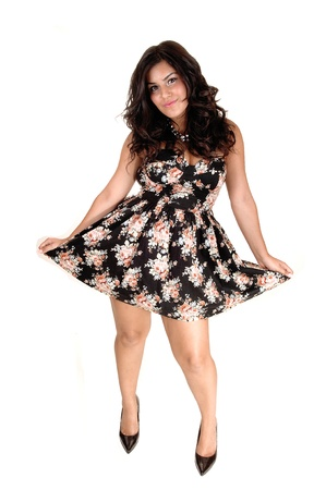 A lovely young teenager in a dress, black with flowers in and long black curly hair, showing her nice dress, for white background. Stock Photo - 10606749