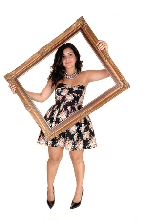 A beautiful young teenager in a nice dress holding up a golden old pictureframe, standing in the studio in high heels for white background. Stock Photo - 10606751