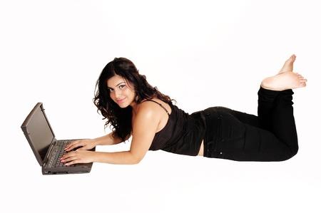 Een mooie tiener in zwarte jeans en korset liggend op haar buik op thefloor en werken op haar laptop, met blote voeten, voor witte achtergrond.
