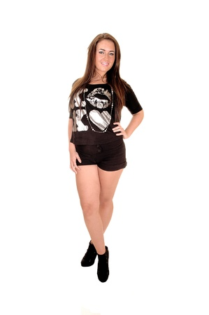 A young woman standing in black shorts and long brunette hairand high heels for white background. Stock Photo - 10655044