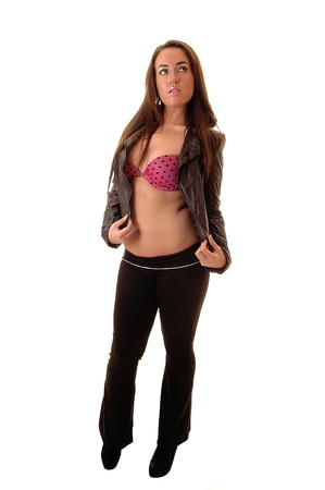 Young woman in long pants, red bra and leather jacket standing in thestudio, showing her nice figure, for white background. photo