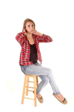 ジーンズと白の市松模様の shirtfor 背景で椅子に座って、背の高いきれいな女性。