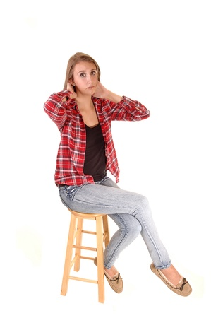 A tall pretty woman sitting on a chair in jeans and a checkered shirtfor white background. Stock Photo