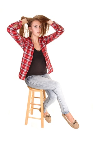 A tall pretty woman sitting on a chair in jeans and a checkered shirtfor white background. photo