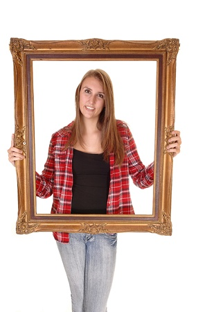 A tall pretty woman holding a picture frame for her upperbody, in jeans and a checkered shirt, over white. photo