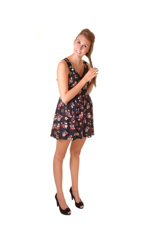 A young tall woman standing in the studio, playing with her hair, in heelsand a short dress, for white background.