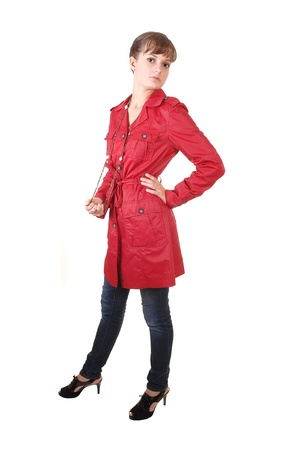 A young pretty teenager standing in a red winter coat an jeans in the studio, for white background. Stock Photo - 10880927