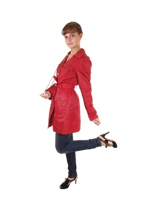 A young pretty teenager standing in a red winter coat an jeans in the studio, for white background. photo