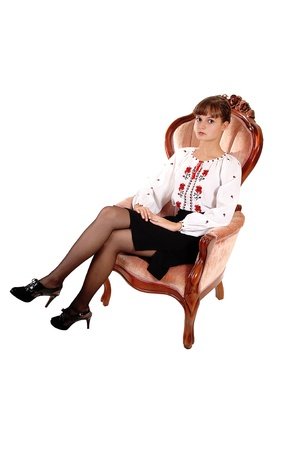 An gorgeous teenager girl in a blouse with red embroidery in a blackskirt sitting in a pink armchair for a portrait, for white background. photo