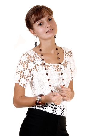 A beautiful teenage girl standing for a portrait in the studio in black shortsand a white blouse with a necklace, for white background. photo
