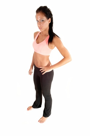 An young woman standing bare feet in the studio with in a pink sports braan long black pants, showing her fit body, for white background. photo