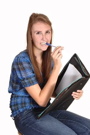 A teenager schoolgirl, with her pen in her mouth, thinking about her homework, in jeans and a chickened blue blouse, over white. photo