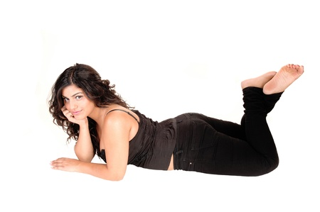 A young pretty girl lying on her stomach on the floor, bare feet and inblack jeans, smiling into the camera, for white background. Stock Photo - 11012001