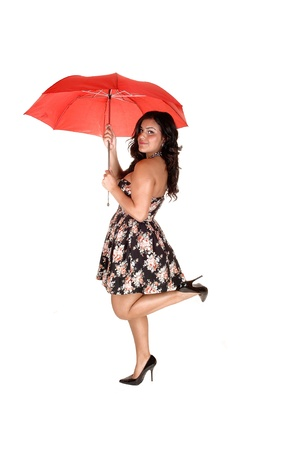 A young pretty girl standing in high heels and a nice dress, holding ared umbrella up, for white background. photo