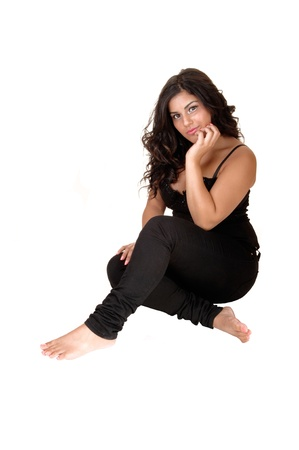 A beautiful girl in black jeans and bare feet with long black curly hairsitting on the floor for white background. photo