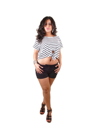 A pretty teenager standing in shorts in the studio having her t-shirt upand showing her belly button, for white background.