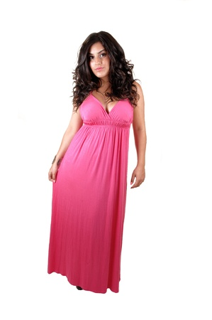 A teenager in a long pink dress, ready for the prom, with long blackcurly hair, standing in the studio for white background. photo