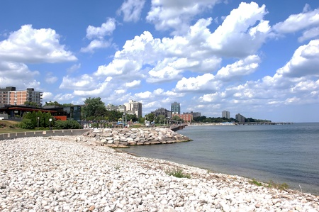 Promenade on the shore of lake Ontario with stones in front and a beautiful blue sky and white clouds in Burlington Ontario.