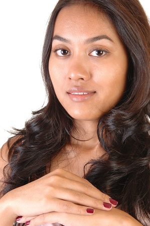 A portrait shoot of a beautiful Asian woman with long brunette curlyhair, looking onto the camera, over white. photo