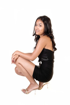 A slim pretty Asian woman crouch on the floor in a black dress and heelswith her long curly brunette hair, smiling, on white background. photo