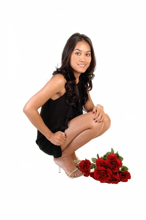 A lovely Asian girl crouching on the floor in a black dress and heelswith a bunch of red roses to her feet, over white background. photo