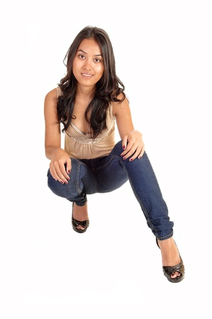 crouched: A slim and pretty Asian woman crouching on the floor in jeans and withlong brunette hair, for white background. Stock Photo