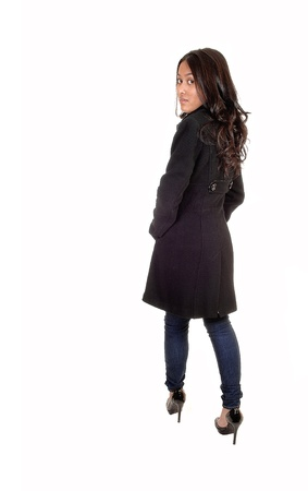 A young Asian woman in a gray winter coat and jeans standing and looking over her shoulder with long brunette hair, for white background. photo