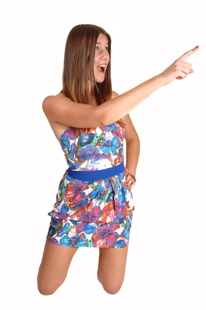 A pretty teenage girl kneeling on the floor in a colorful dress and pointingwith her finger, with long dark blond hair, for white background. photo