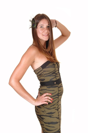 A lovely teenage girl in an olive tight strapless dress standing in the studio with a feather in her long hair, for white background. photo