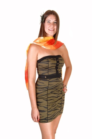 A beautiful teenage girl in a tight olive green dress and a yellow redscarf around her heck, standing in the studio for white background. photo