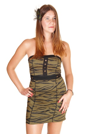 Teenage girl in a strapless olive green tight dress and a feather in herhair standing from the front in the studio, for white background. photo