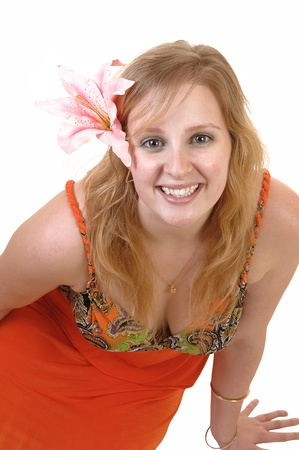 A beautiful blond teenager sitting on the floor, smiling into the camera witha pink lily in her hair and in a colorful orange dress, for white background. photo