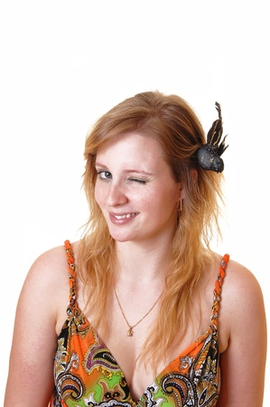 A pretty teenage girl sitting in the studio blinking with one eye and flirtingwith the photographer, with a black bird in her blond hair, over white. photo