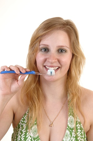 A young teenage girl in a green dress with a toothbrush in her mouthbrushing her teeth, for white background. photo