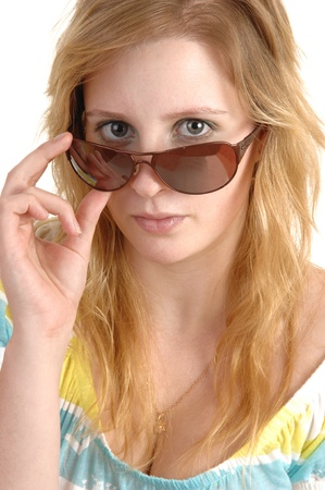 A lovely teenage girl in closeup holding her sunglasses and lookingover the frame, with blond hair and necklace, over white background. photo
