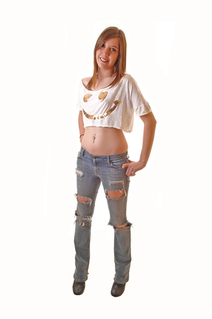 Young teenage girl standing in ripped jeans and a short t-shirt in thestudio, smiling, on white background. Stock Photo - 11495541