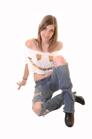 A lovely blond teenager girl sitting on the floor in a ripped jeans and anshort blouse with a gold face on, for white background. Stock Photo - 11495549