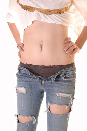 An young woman standing with her ripped jeans open and her pantiesshowing, showing her flat stomach with belly button jewellery, over white. photo