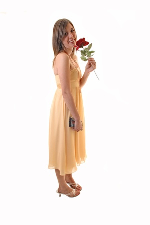 Lovely young woman in a yellow long dress with her purse in her hand and a red rose she smells, in high heels for white background. photo