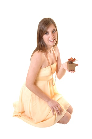 A gorgeous girl kneeling on the floor in the studio and holding a smallgift in her hand, for white background. photo