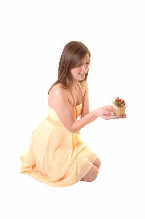 A lovely girl kneeling on the floor in the studio in a yellow dress holdinga little gift with both hands and looking at it, for white background.
