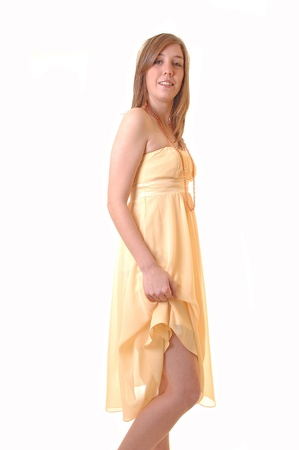 A young woman standing in a yellow long dress and lifting one site upto show her legs, for white background. Stock Photo - 11495546