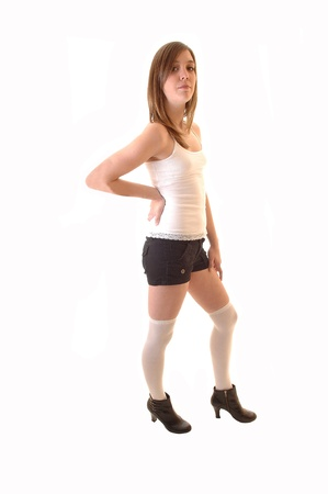 A young pretty woman in black shorts and a white t-shirt standing in thestudio wearing leggings, looking into the camera, over white background. Фото со стока