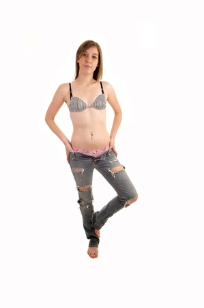 pink panties: A young slim woman in ripped jeans and bra standing in the studio barefeet and showing her pink panties, for white background. Stock Photo