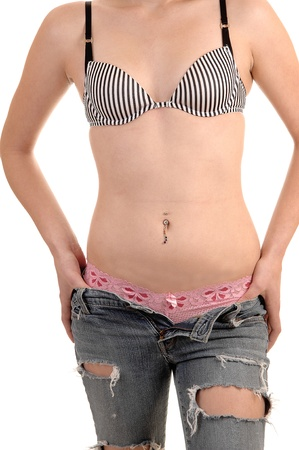 unbuttoned: The mid-section of a slim woman with the bra, panties and ripped jeanswith jewellery in the bellybutton, foe white background.