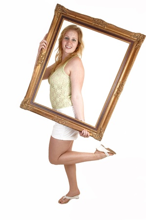A blond pretty woman in heels and a white shorts and green top, holdinga picture frame in front of her, standing for white background. photo