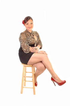 A young pretty woman in a short black skirt and brown blouse with redheels sitting on a bar chair with a flower in her hair, for white background.
