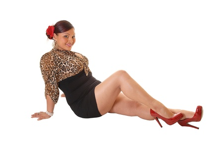A happy young woman sitting on the floor in a short skirt and red heelswith a flower in her hair, showing her nice legs, for white background.