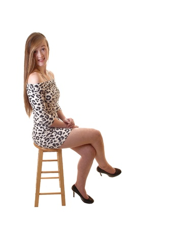 A slim and pretty teenager girl sitting on a chair in a leopard print dressand long brunette hair and high heels, smiling into the camera, over white. Фото со стока