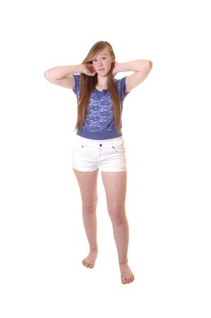 Een jong tienermeisje in witte broek en blauwe blouse staan blote feetin de studio, het spelen met haar lange donkerbruine haar voor een witte achtergrond.